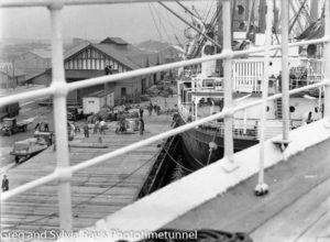 Newcastle's Lee Wharf, seen through the rails of a berthed ship. Almost certainly the ship in front is the Largs Bay, being loaded with butter in June 1936.