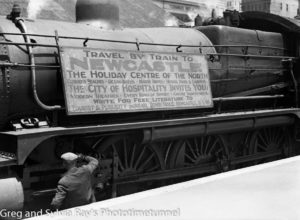 """Travel by Train to Newcastle"":  tourist advertisement on the side of a steam engine at Newcastle Railway Station. Circa 1930s."