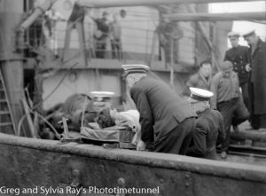 Injured seamen being carried off the torpedo-damaged ship Allara in Newcastle Harbour, July 1942. (4)