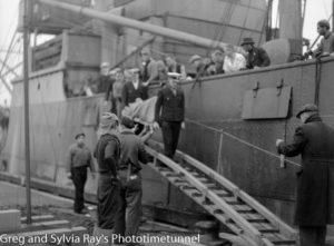 Injured seamen being carried off the torpedo-damaged ship Allara in Newcastle Harbour, July 1942. (6)