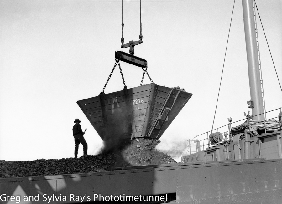Coal spilling from a wooden hopper into the hold of a ship at Carrington, September 14, 1937.