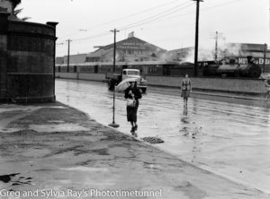 Steam locomotive in background on a rainy day in Scott Street, Newcastle, March 23, 1939.