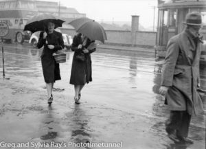 Women with umbrellas on Scott Street, Newcastle. Circa 1940s.