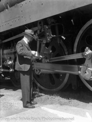 Man oiling locomotive engine wheel.