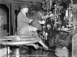 Fireman feeds the boiler in the cabin of a steam locomotive, December 19, 1940. (2)