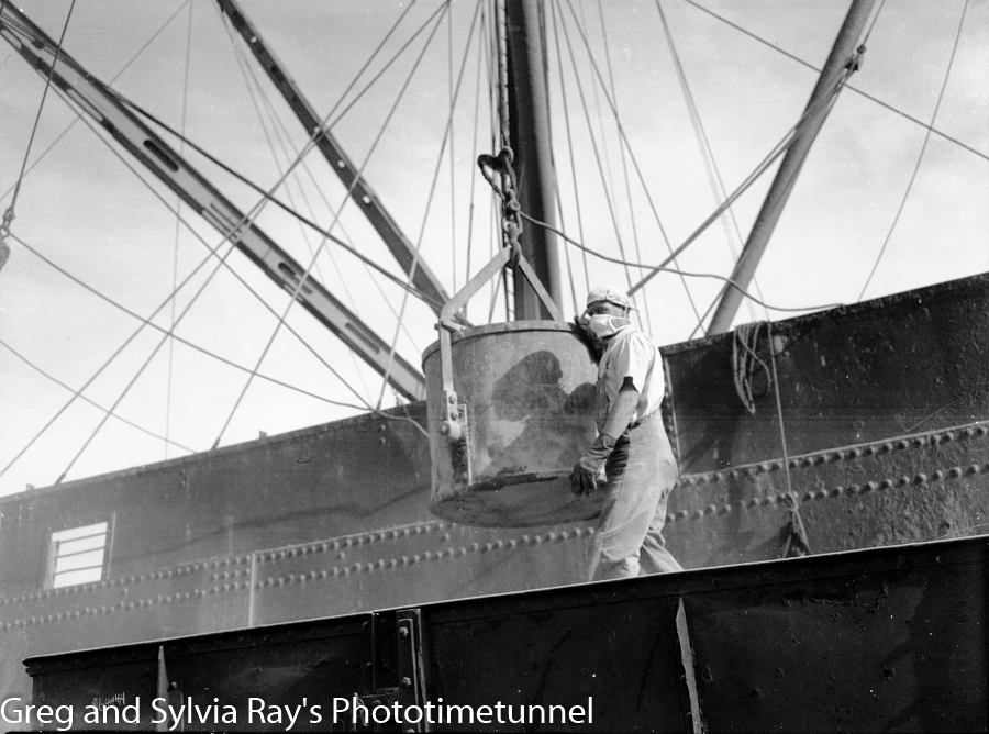 Transferring phosphate between the ship AguiIlos and rail cars, Newcastle Harbour, late 1940s.