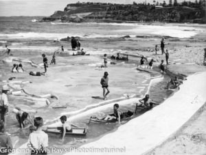 Children paddle corrugated iron canoes in Newcastle's Young Mariners Pool.