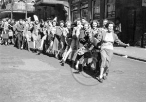 Conga line of revellers in Newcastle, NSW, at the end of World War 2, August 15, 1945.