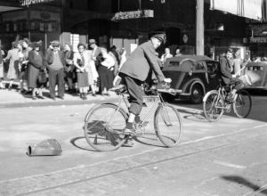 Cyclist dragging a tin: celebrations in Newcastle, NSW, for the end of World War 2, August 15, 1945.