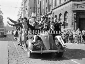 Girls on a car. Celebrations in Newcastle, NSW, for the end of World War 2, August 15, 1945.