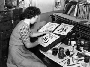 Ticket-writer making new signs for ration coupon shopping in a Newcastle department store, June 1, 1942.