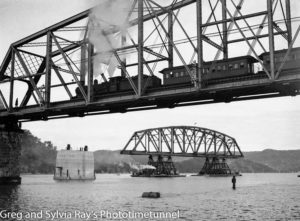 Steam locomotive crossing the old Hawkesbury River railway bridge while the first span of the new bridge is floated into place.