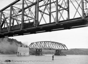 Steam locomotive crossing the old Hawkesbury River railway bridge while the first span of the new bridge is floated to its position, September 15, 1944. (3)