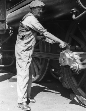 Oiling the wheels of a steam locomotive.