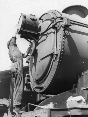 Cleaning the headlight of a 36-class steam locomotive, circa 1940s.