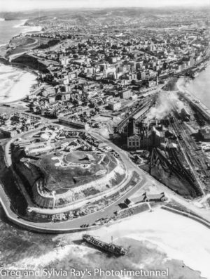 Aerial photograph of Nobbys Beach and Fort Scratchley, Newcastle, 1940, showing the grounded ship TSS Maianbar, with Zaara Street power station in the background.
