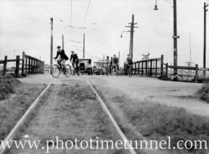 Cyclists crossing the Port Waratah tramline, Newcastle, NSW, November 18, 1938. (2)