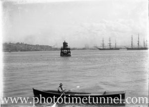 View of Newcastle Harbour, with sailing ships in the background and a rowboat in foreground. Circa 1910.