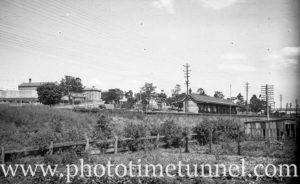 View of East Maitland railway station, NSW, with gaol in left background. Circa 1930s.
