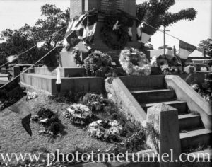 Flags and floral wreaths at East Maitland war memorial, NSW, circa 1930s.