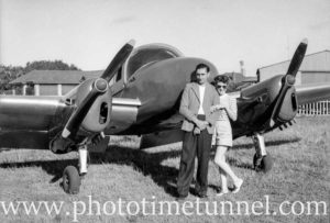 Couple standing in front of a Miles Gemini aircraft. Circa 1948.