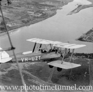 Tiger Moth aircraft over the Hunter River estuary, Newcastle, NSW, circa 1940s, showing BHP steelworks.
