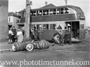 Double-decker bus stands near spilt barrels on King Street, Newcastle, NSW.