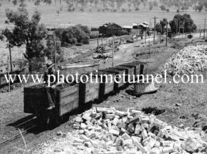 Man sitting on coal wagons at a Hunter Valley colliery, NSW, circa 1940s.