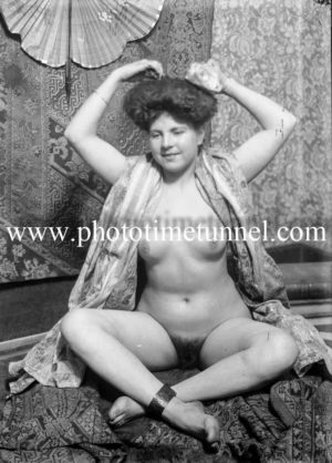 Vintage studio portrait of nude woman draped in a scarf.