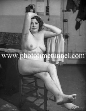 Vintage photo of mature nude woman on chair.