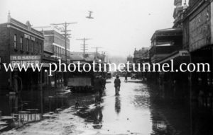 Tram and cycles in flooded High Street Maitland
