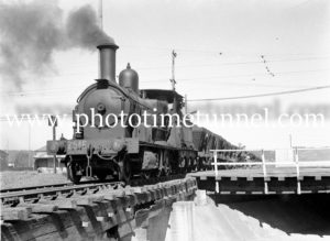 Coal train and cyclists at the Gully Line crossing, Broadmeadow, NSW, August 5, 1946.