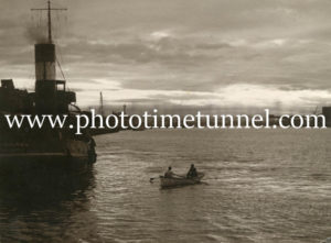 Rowing boat near the tug St Hilary in Newcastle Harbour, NSW. Moody sepia view.