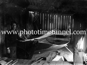 Young man in a boatbuilder's shed, circa 1910.