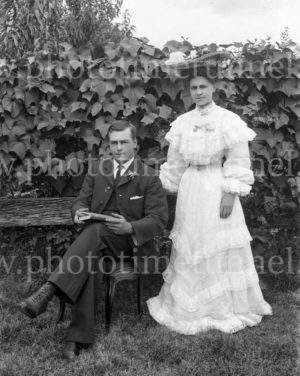 Portrait of a couple, man seated, woman in white dress standing. Circa 1910.