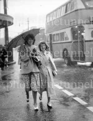 Two girls with an umbrella on a rainy day in Hunter Street, Newcastle, circa 1940s.