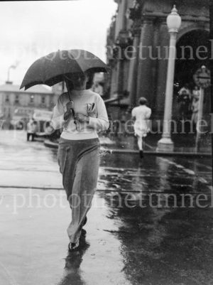 Woman with umbrella outside Newcastle post office on a rainy day, circa 1940s.