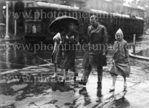 Family crossing Bolton Street on a rainy day in Newcastle, circa 1940s.