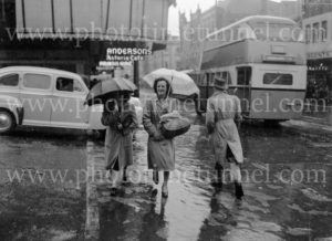 Double decker bus and shoppers with umbrellas on a rainy day in Hunter Street, Newcastle, circa 1940s.