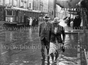 Older couple on a rainy day in Hunter Street, Newcastle, 1938.