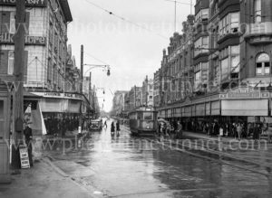 Tram and shoppers at Scotts Corner, Hunter Street, on a rainy day, March 11, 1937.