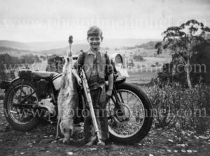 Boy with motorcycle, rifle and dead kangaroo.