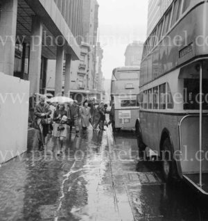 Double-decker buses on a rainy day in Sydney, circa 1960s.