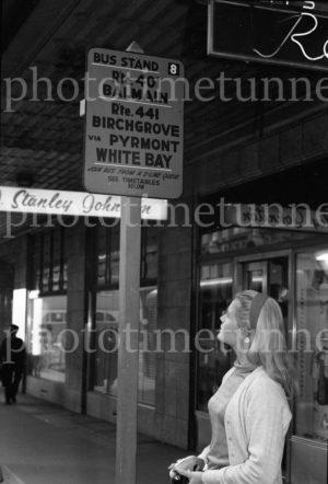 """Balmain bus"": Blonde woman waiting at a bus stop in Sydney, circa 1960s."