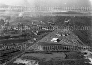 Aerial view of the BHP steelworks, Newcastle, NSW, showing the administration building and carpark, 1960s. (3)