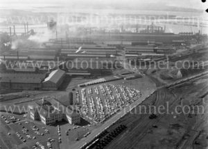 Aerial view of the BHP steelworks, Newcastle, NSW, showing the administration building and carpark, 1960s. (2)