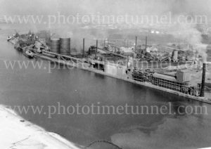 Aerial view of the BHP steelworks, Newcastle, NSW, showing the channel and wharves,1960s.