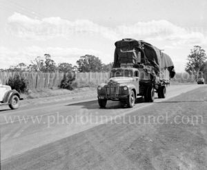 Heavily loaded truck on a road in Victoria, circa 1950.
