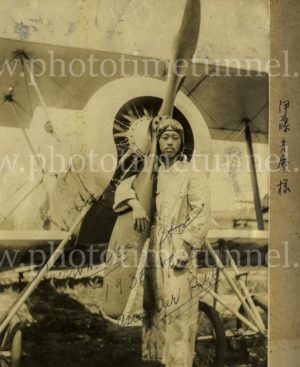 Japanese man holding the propeller of a biplane, circa 1936.