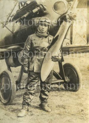 Japanese airman holding the propeller of a biplane, circa 1936.